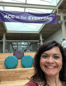 """Photo of Dr. Lydia CdeBaca standing in front of a banner that reads """"ACC is for EVERYONE!""""."""