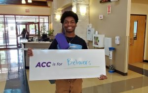 student holding ACC is for believers sign