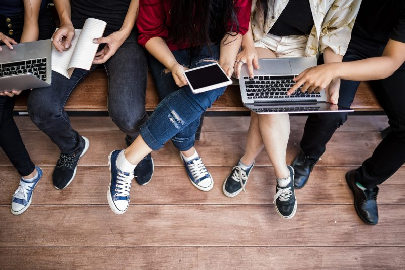 Students on a bench with laptops and digital devices